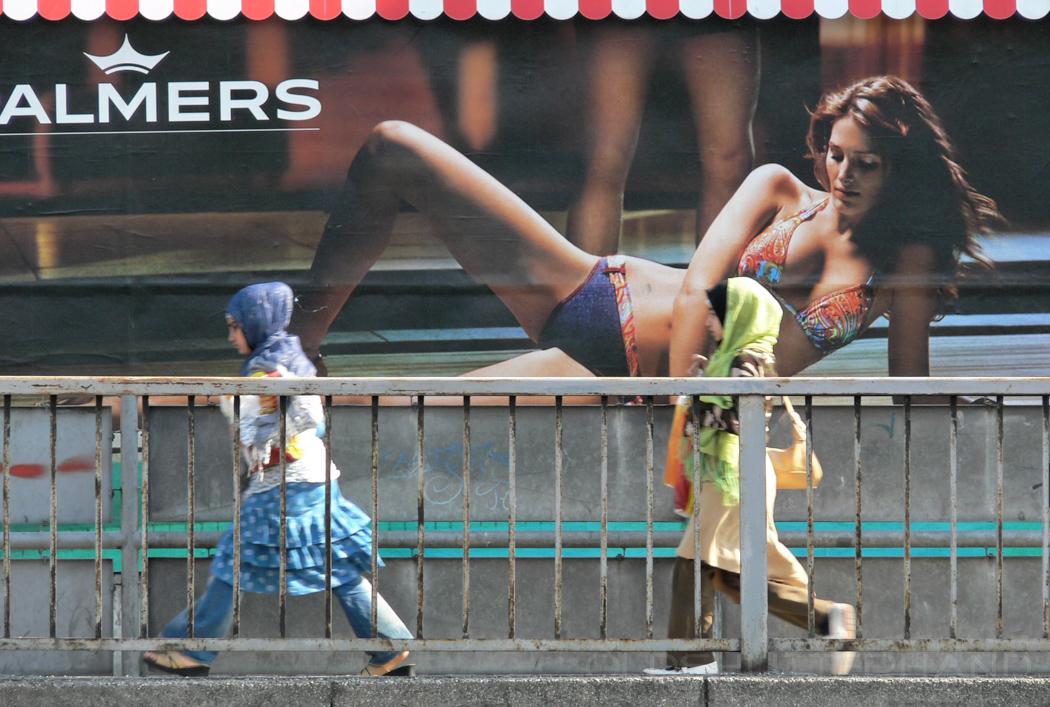 Palmers Reklamewand mit vorbeilaufenden Frauen