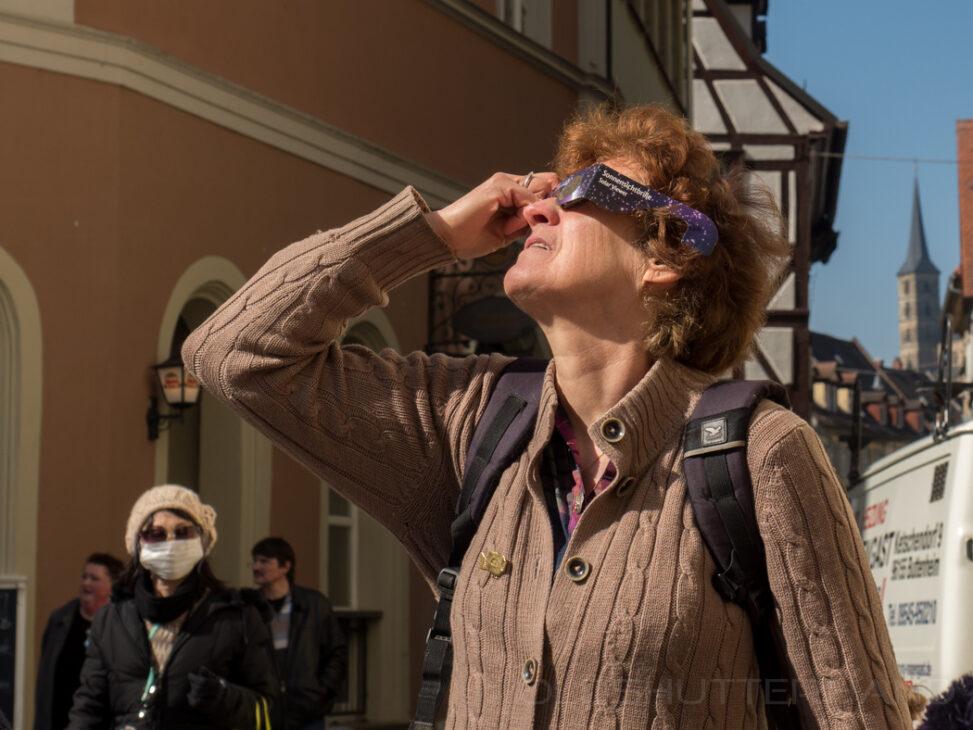 Frau beim beobachten der Sonnenfinsternis 2015